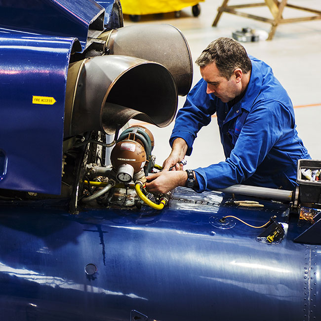Aerospace engineer in blue boiler suit working on an engine.