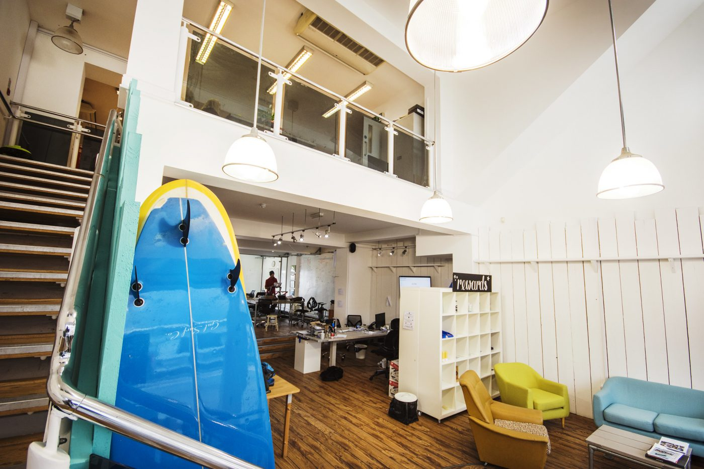 Surfboards in a studio with wooden floors and a mezzanine.