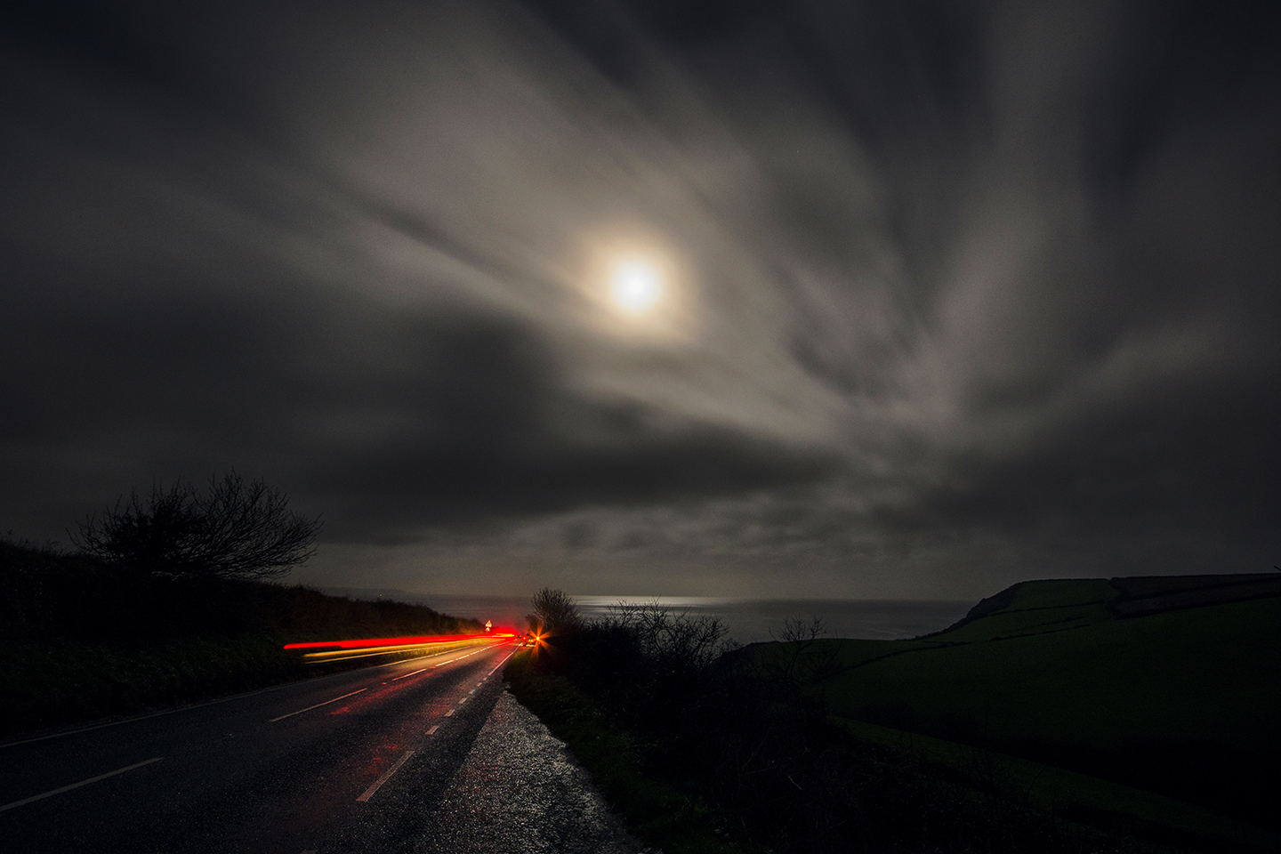 Road at night time with lights showing from cars and a full moon in the sky.