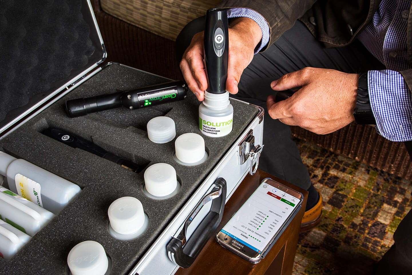 Person using tool to place cylinders into a briefcase.