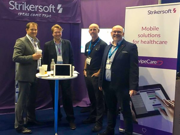 Strikersoft team at a conference in front of purple background.
