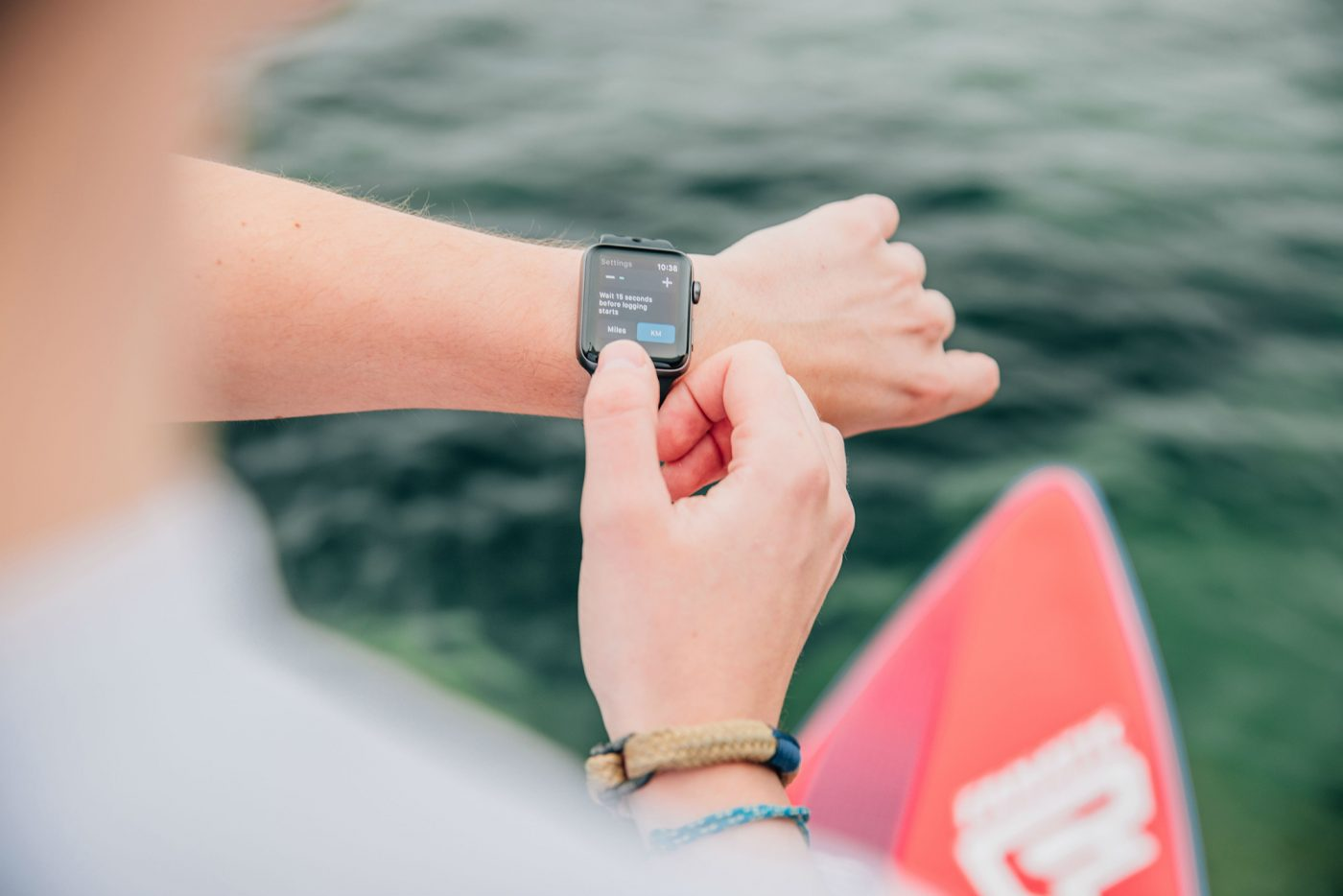 Man using digital watch while standing on a paddleboard.