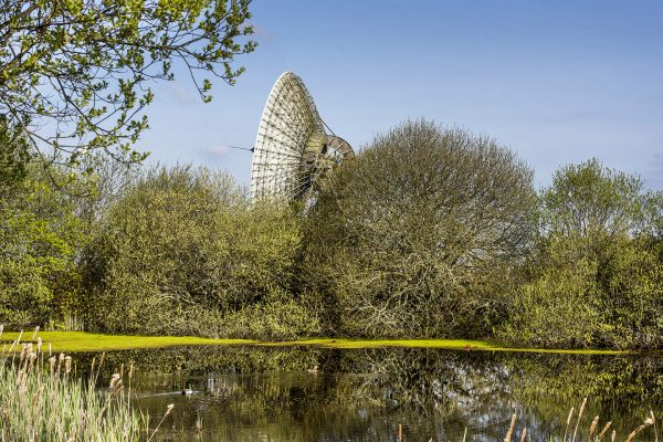 Goonhilly Earth Station behind some green trees and a lake.