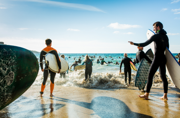 People in wetsuits with surfboards on the beach.