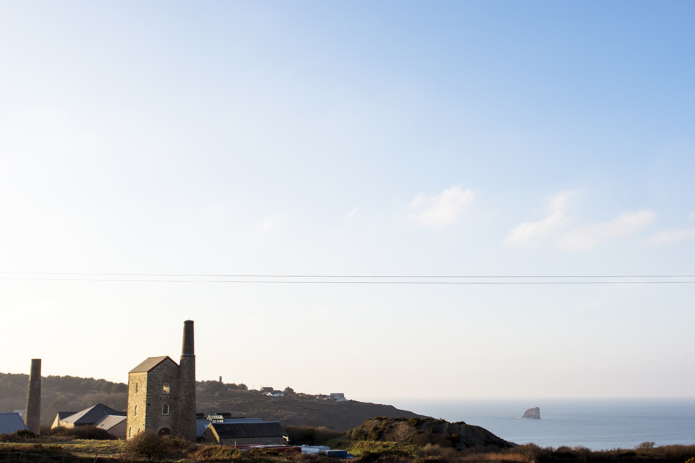 Landscape of Cornwall coast with an engine house and the sea.