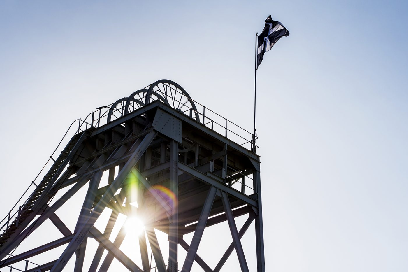 A mine shaft photographed from below with the Cornish flag flying.