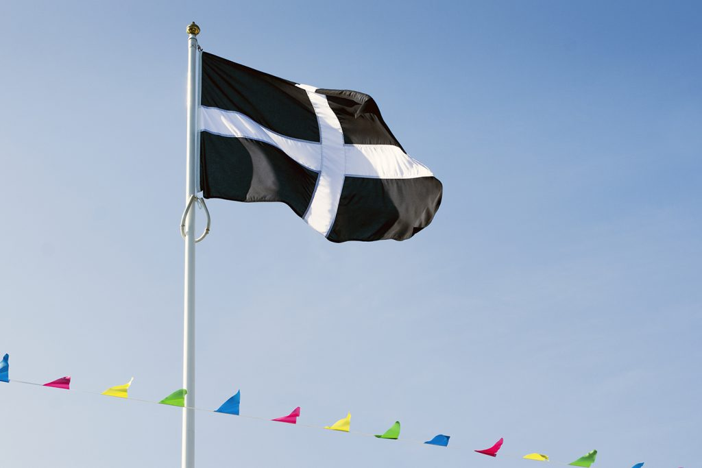 St Piran's Flag against blue sky with colourful bunting below.
