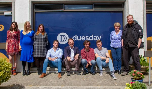 Duesday Team photographed against a billboard.
