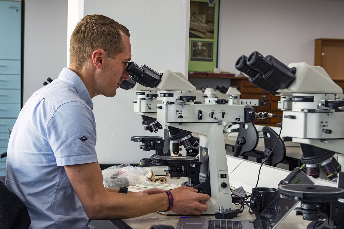 Man in blue shirt looking through microscope on a desk.