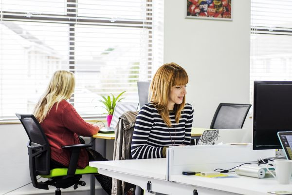 Woman in stripy top working on a laptop at a desk.