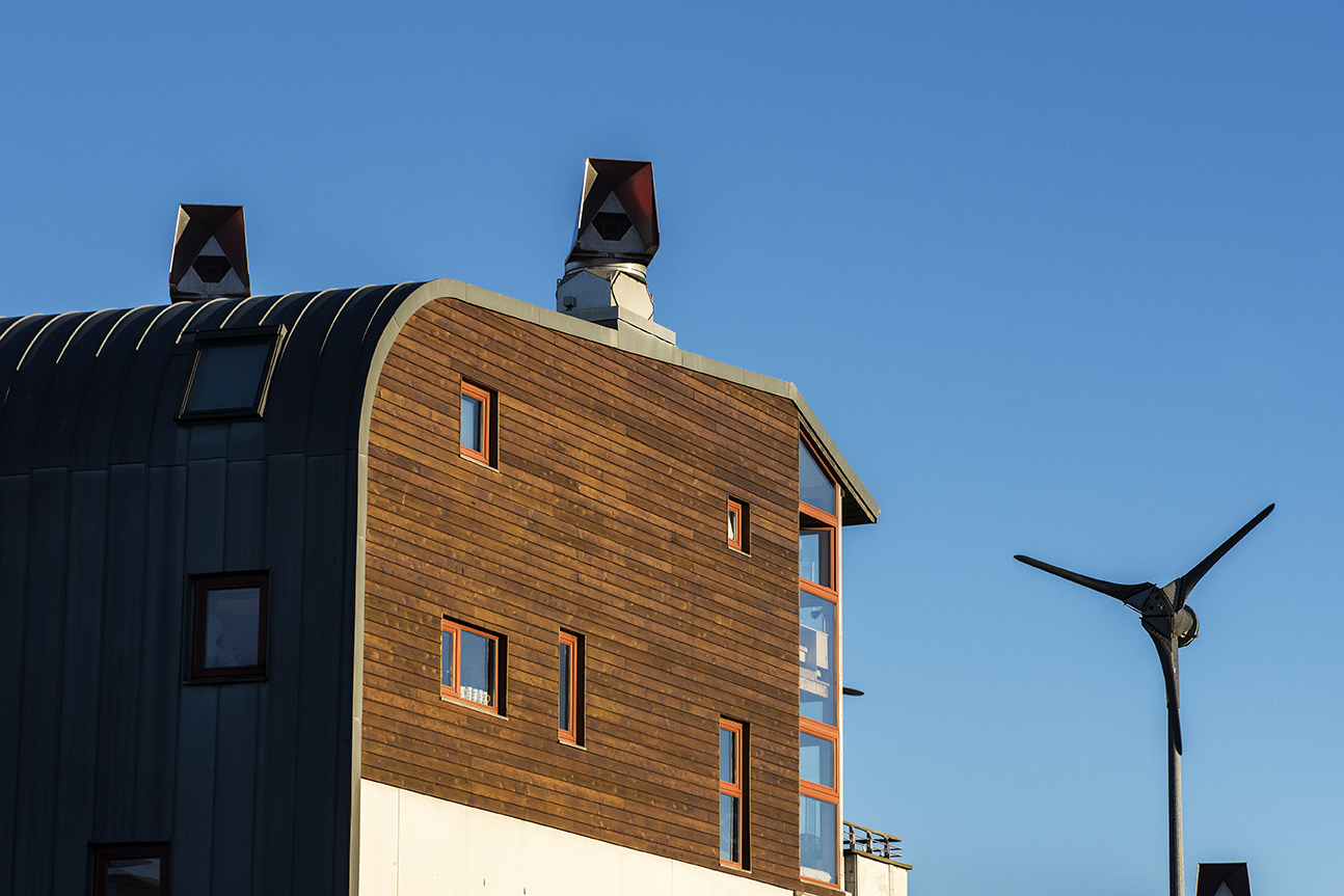 Wooden panelled building with wind turbine in the background.