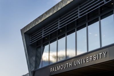 Front windows and edge of building at Falmouth University with signage on the front.